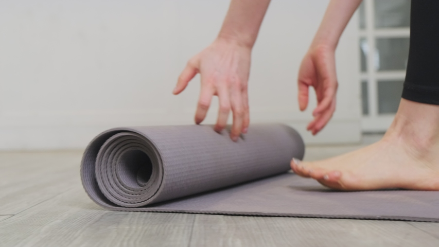 B roll shot of woman roll out yoga mat for preparation. Close up view on hand when open mat. Young beautiful fit sport woman work out by exercise yoga in living room at home during covid19 pandemic. Royalty-Free Stock Footage #1056856904