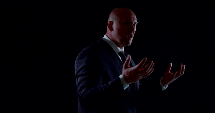 The bald man is dressed in a dark business suit. he spins slowly against the black background, gets angry, yells, shakes his hands, then agrees and gives a thumbs-up