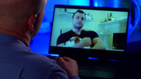 a man communicates via video link with his friend. the guy holds the dog in his arms. over-the-shoulder view of the laptop. contour blue light