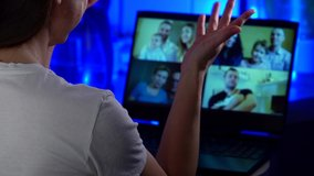 the woman communicates via video link with several families at once. over-the-shoulder view of the laptop. contour blue light