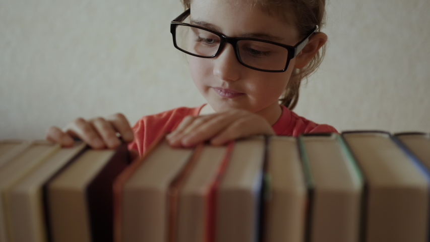 Little Girl Child Choose Books on Shelf. Young Schoolgirl in Glasses Taking Books From Shelf and Flipping Through Pages in Library.  Book Reading Hobby. Royalty-Free Stock Footage #1056864104