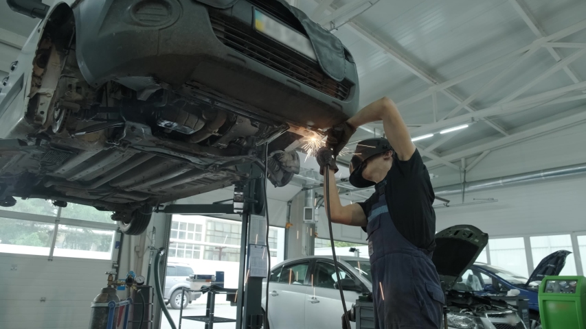 Car service worker welds and repairs an exhaust pipe of a car. Close-up welding work on a lifted car. View from the back. Mechanic welds the bottom of the car. | Shutterstock HD Video #1056867140