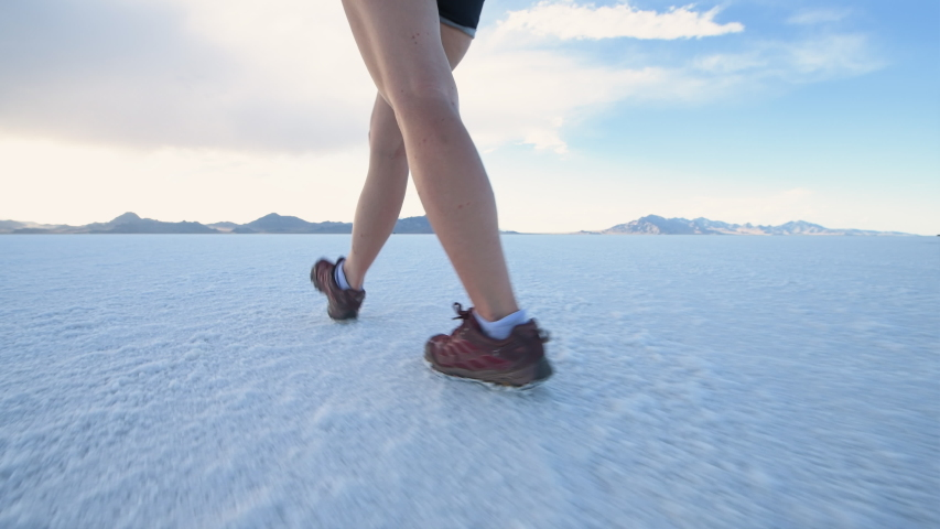 Point of view panning of young girl person people legs feet shoes ground level walking texture of Bonneville salt flats