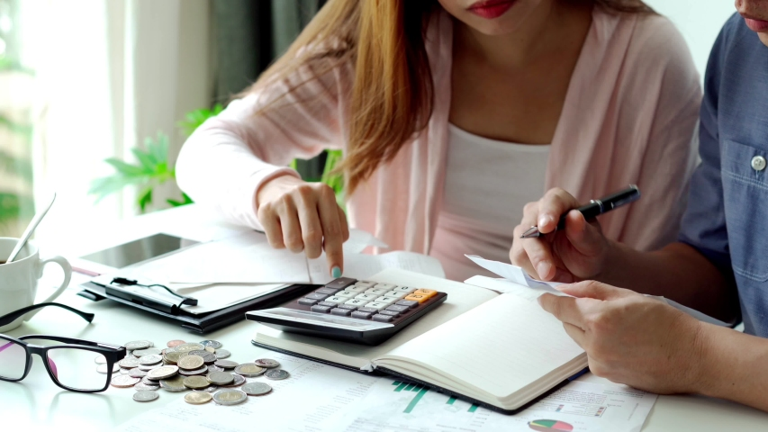 Stressed young couple calculating monthly home expenses, taxes, bank account balance and credit card bills payment, Income is not enough for expenses | Shutterstock HD Video #1056868520