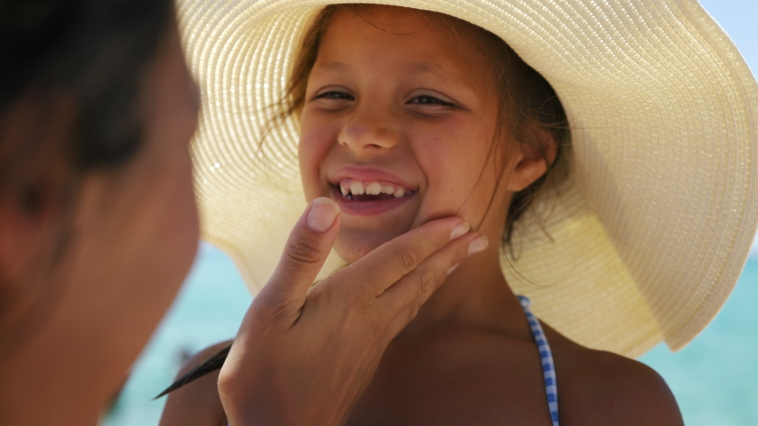 Close up of young mother is applying protective sunscreen or sunblock lotion on her little happy smiling daughter's face to take care of skin on a seaside beach during family holidays vacation.