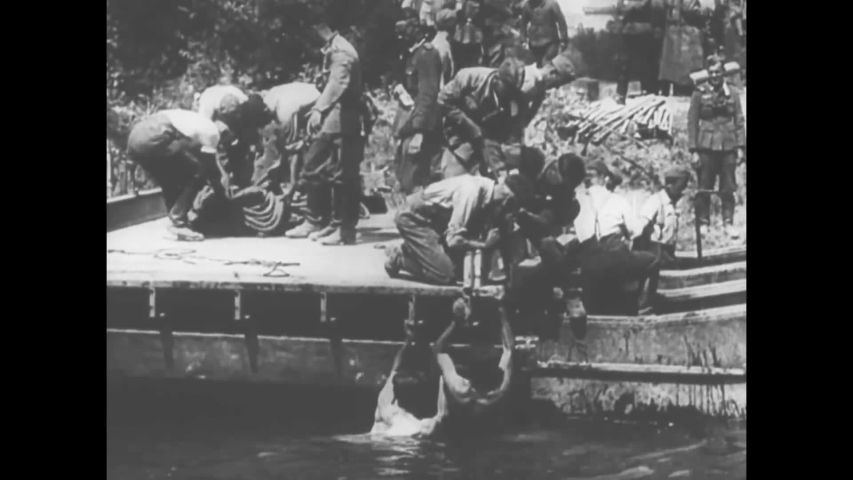 CIRCA 1940 - In this documentary directed by Frank Capra, Nazi soldiers cross the Meuse River from the Ardennes Forest in France.