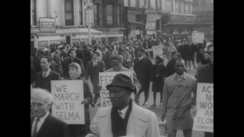 CIRCA 1965 - Black and white protestors march in Harlem, New York in solidarity with Selma, mourning the murder of Reverend James J. Reeb.