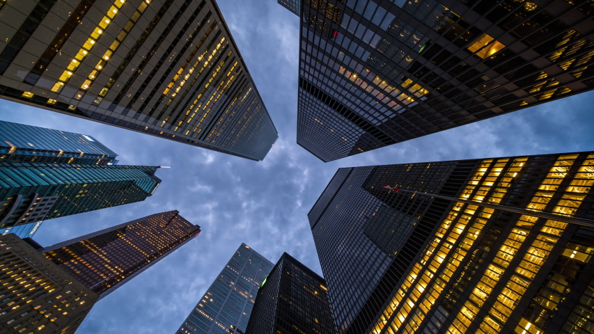 Business and finance concept, moody time lapse view looking up at modern office building architecture in the Toronto financial district, Ontario, Canada.