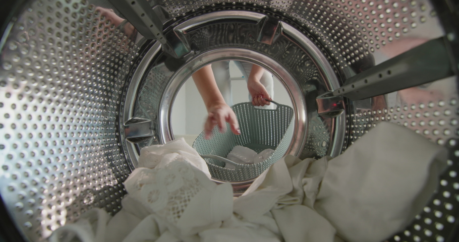 A woman pulls clean washed white linen from the washing machine
