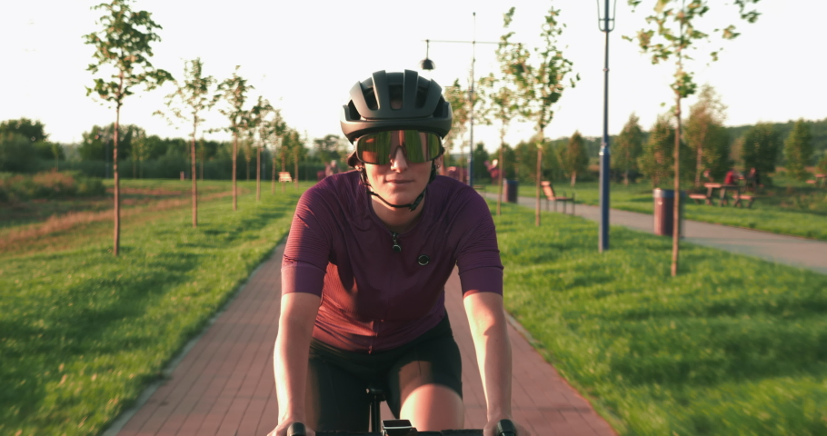 Fit athletic cyclist is spinning pedals on road aero bike in sunshines. Portrait of young female athlete is pedaling on bicycle on cycle path at sunset. Happy motivated woman is cycling on bicycle