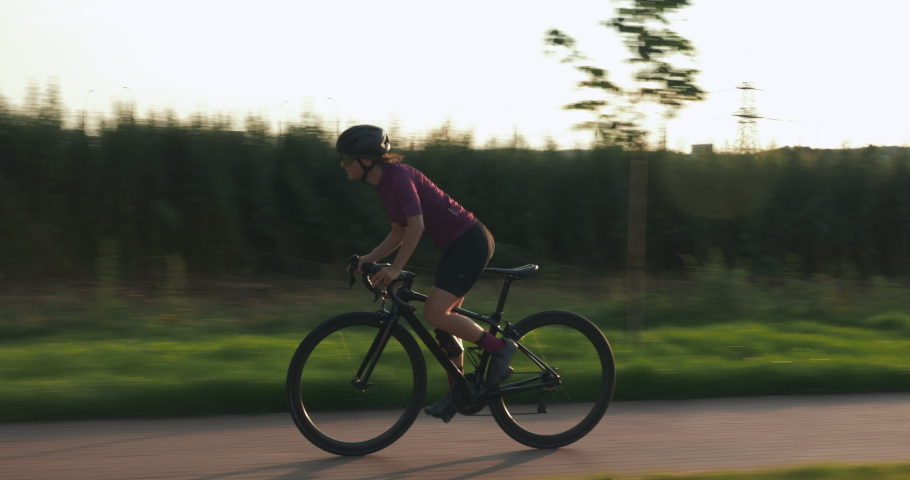 Female pro cyclist is hard pedaling on road aero bike at sunset. Woman athlete is training on bicycle and preparing for competition race. Professional triathlete is cycling at sunset. Cycling concept