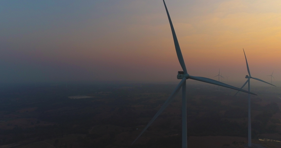 Aerial view of Wind turbines Energy Production- 4k aerial shot on sunset. 4k drone footage turbines at sunrise with clouds | Shutterstock HD Video #1056894803