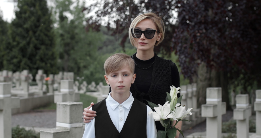 Portrait of woman in dark glasses with flower and her son looking to to camera. Young kid holding american flag while standing with his mom at cemetery. Concept of memorial day.