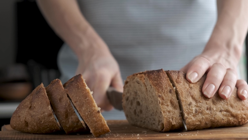 Woman cutting bread at the kitchen. Slicing bread to make a sandwich. Cooking process 4k resolution footage