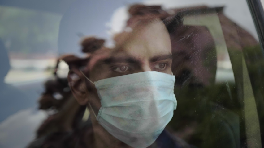 A man/ male sitting in the car wearing face protective mask looking outside through the glass window amid Corona virus/ COVID 19 epidemic or pandemic Royalty-Free Stock Footage #1056897491