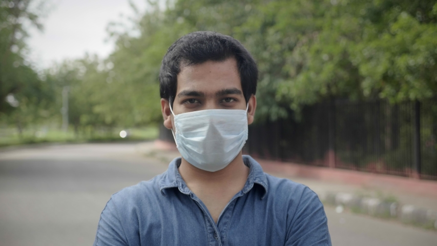 A close shot of a happy young man male standing outdoors removes the face protective mask and smiles looking at the camera lens amid Corona virus COVID 19 epidemic or pandemic | Shutterstock HD Video #1056897497
