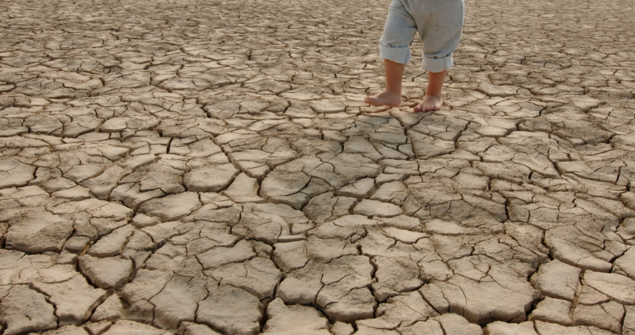 Close up shot of legs of baby boy running on cracked soil, destroyed by overuse, climate change and flood - ecological issues, save our planet 4k footage Royalty-Free Stock Footage #1056897602