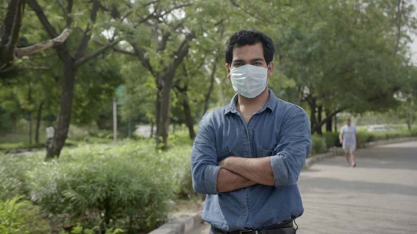A young handsome man standing with arms crossed outdoors along the street wearing face protective mask looking at the camera amid Corona virus/ COVID 19 epidemic or pandemic