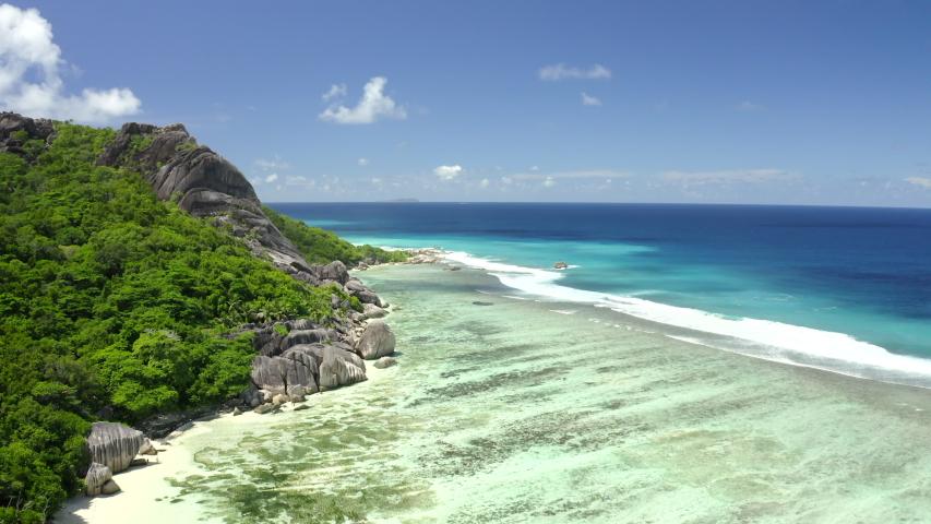 Dron view Anse source d'argent azure sea water (Indian Ocean), La Digue, Seychelles islands vacation, UHD 4K part 4   Shutterstock HD Video #1056899807