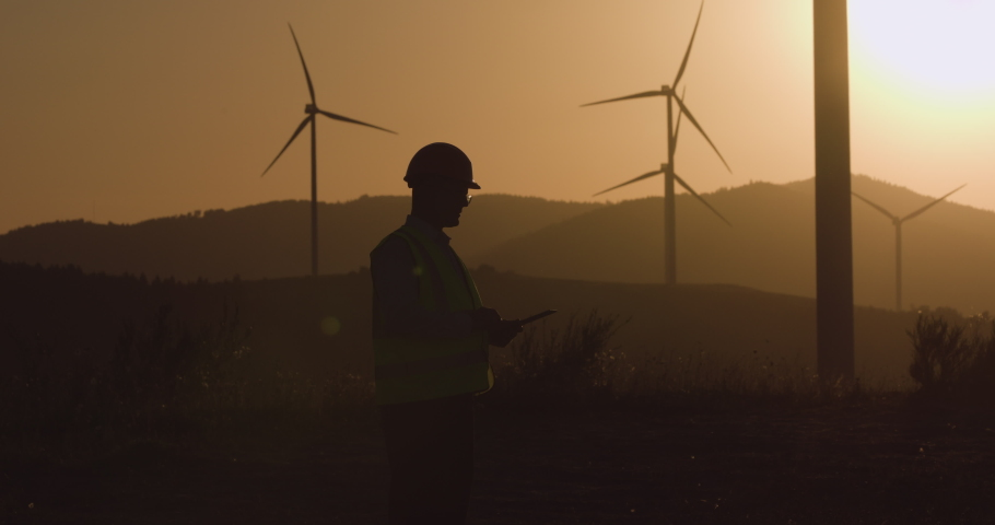 Engineer looks at the information in the tablet, turning his head in the direction of the windmill at sunset