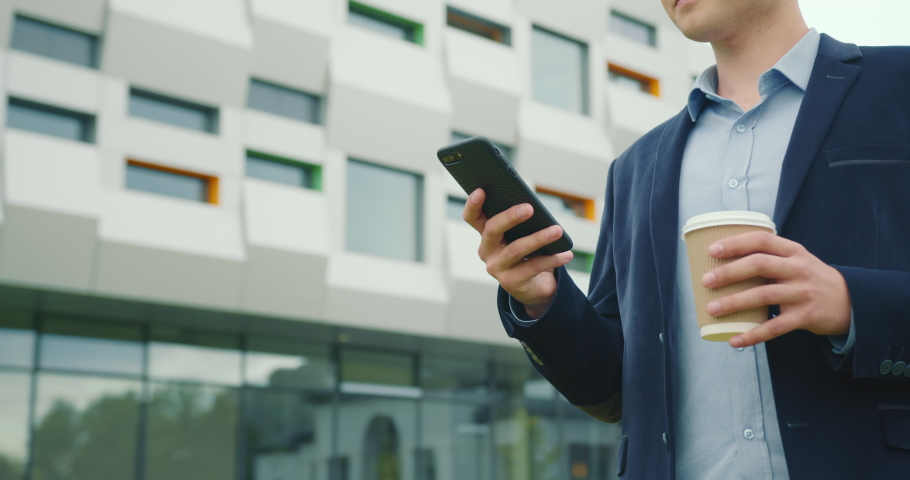A businessman is walking near the business center with a cup of coffee in his hand. He is texting on a smartphone. He is wearing a suit and glasses. Close-up shooting. 4K