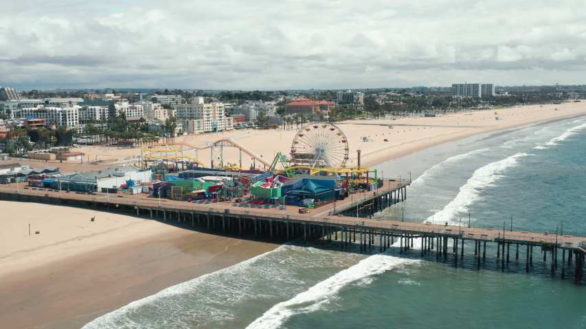 Santa Monica Pier on cloudy day, Los Angeles. The footage of the Santa Monica pier and the amusement park from the side of the ocean. Beautiful panorama of the city skyline is seen behind sandy beach