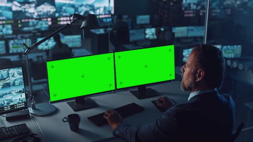 Male Officer Works on a Computer with Two Green Screen Mock Ups in Surveillance Center in a Harbour Monitoring Center with Multiple Cameras on a Big Digital Screen. Employees Sit in Front of Displays. Royalty-Free Stock Footage #1056907760