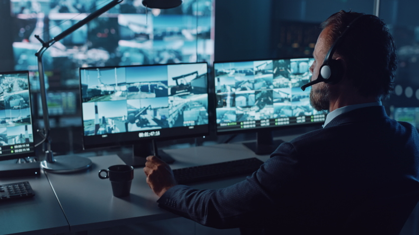 Male Officer Works on a Computer with Surveillance CCTV Video Footage in a Harbour Monitoring Center with Multiple Cameras on a Big Digital Screen. Employees Sit in Front of Displays with Big Data. Royalty-Free Stock Footage #1056907763