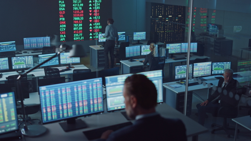 Professional Financial Data Analysts Working in a Modern Monitoring Office with Live Analytics Feed on a Big Digital Screen. Monitoring Room with Finance Specialists Sit in Front of Computers. Royalty-Free Stock Footage #1056907799