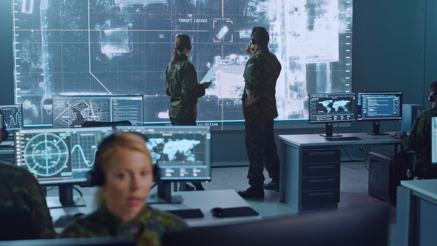 Military Surveillance Team of Officers Locked a Target on a Vehicle from a Satellite and Monitor it on a Big Display in Office for Cyber Operations for Managing Security and Army Communications. Royalty-Free Stock Footage #1056907844