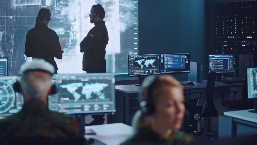Shifting Focus Between Military Surveillance Officers Working in a Central Office Hub for Cyber Operations, Control and Monitoring for Managing National Security, Technology and Army Communications.