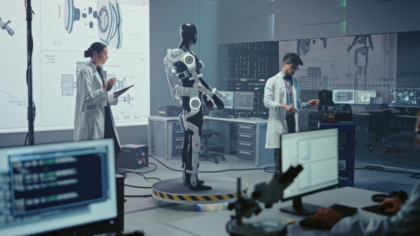 In Robotics Technology Development Laboratory Diverse Team of Engineers Work on a Bionics Exoskeleton Prototype. Scientists Design Powered Armor Suit to Help Disabled People and Hard Labor Workers