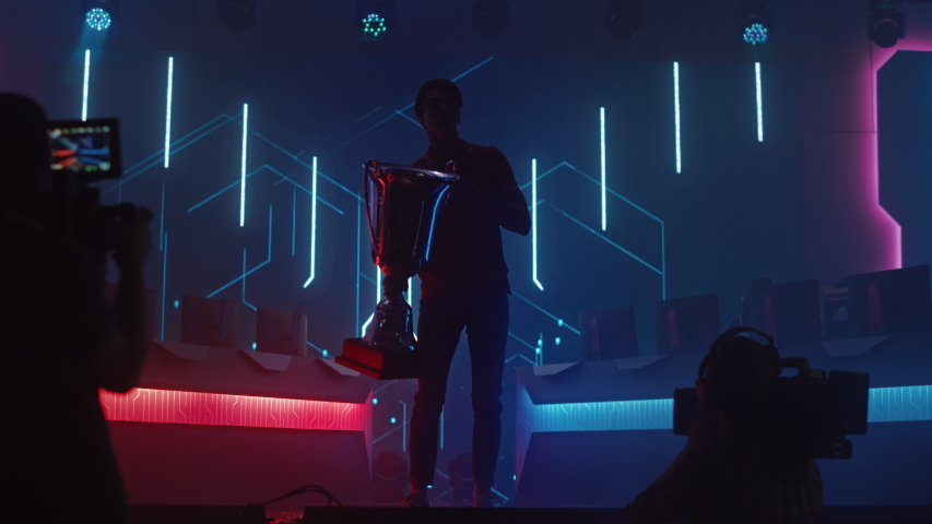 Professional Video Games Player Tournament Winner Celebrates Victory Cheering and Holding Trophy. Big Stylish Neon Bright Championship Arena doing Pro Computer Gaming Event with Online Streaming | Shutterstock HD Video #1056908840