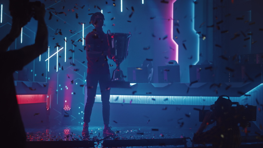 Professional Video Games Player Tournament Winner Celebrates Victory Cheering and Holding Trophy. Big Stylish Neon Bright Championship Arena doing Pro Computer Gaming Event with Online Streaming