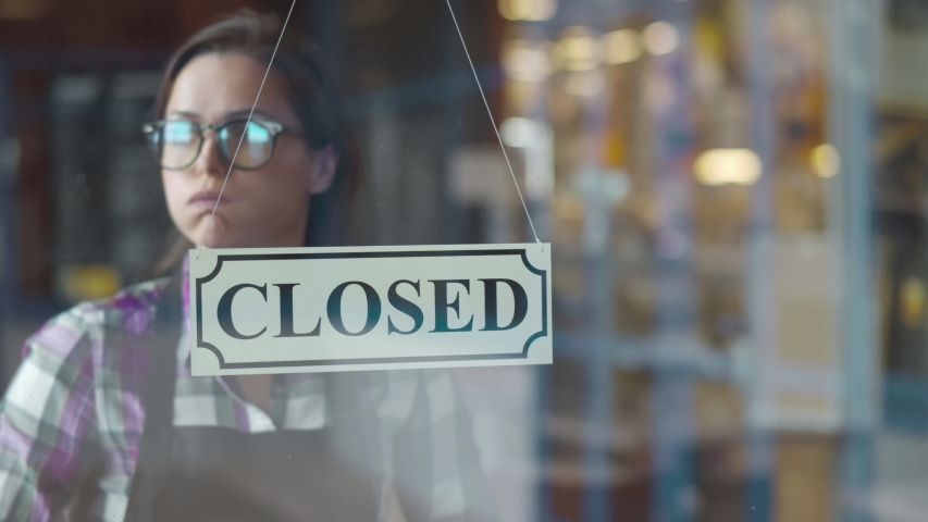 Young tired waitress turning sign to closed on cafe glass door at end of working day. Exhausted coffee shop owner closing place turning sign in evening. Small business development concept Royalty-Free Stock Footage #1056912533