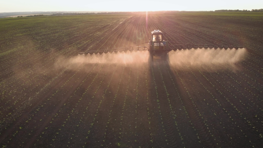 Aerial view of farming tractor spraying on field with sprayer, herbicides and pesticides at sunset. Farm machinery spraying insecticide to the green field, agricultural natural seasonal spring works. Royalty-Free Stock Footage #1056913787