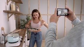 Cropped Footage of a Man Holding Smartphone, Taking Video of Young Woman Cooking Happily in the Kitchen. Amateur Girl Chef Recording Video Recipe for the Blog. Married Couple Having Fun in the Kitchen