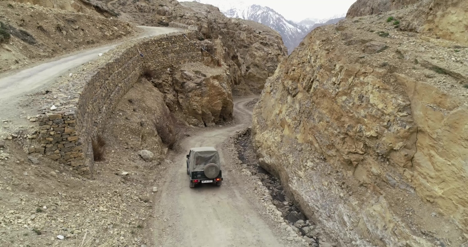 Aerial shot of  4x4 vehicle off roading, 4x4 vehicle on rocky mountains, Drone shot of vehicle on road between 2 rocky mountains | Shutterstock HD Video #1056916343