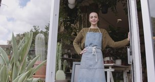 Small business entrepreneur female opening door of plant shop and looking at camera confident