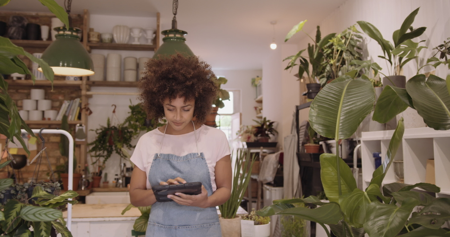 Young adult Afro American female small business owner working on digital tablet in store checking inventory   Shutterstock HD Video #1056918830
