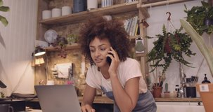 Young adult Afro American female small business owner working on laptop in store and speaking to client on phone
