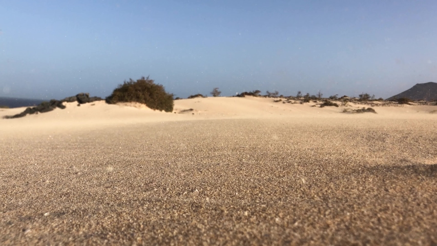 Sand movement caused by strong wind causing a sand storm in the dunes of Corralejo Fuerteventura, Canary Islands | Shutterstock HD Video #1056918890