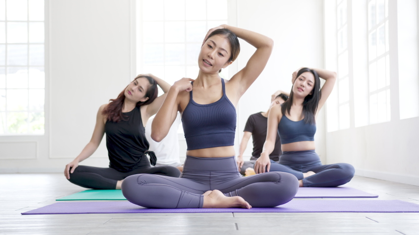 Wide and zoom out shot : Young asian sporty attractive people practicing yoga lesson with instructor. Asia group exercising and stretching healthy lifestyle in fitness studio and  gymnastics class | Shutterstock HD Video #1056923606