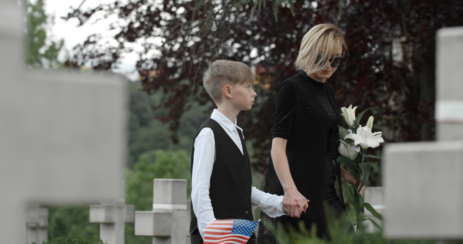 Young widow with flower holding her son hand while walking. Teen kid with american flag looking at his mother while going to honour his father at cemetery Concept of memorial day.