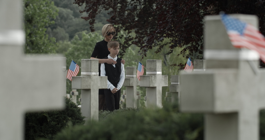 Mother and her teen son putting white lily flowers at cemetery. Widow and kid holding hands, walking and stopping near gravestone. Concept of memorial day. American flags on stone crosses.