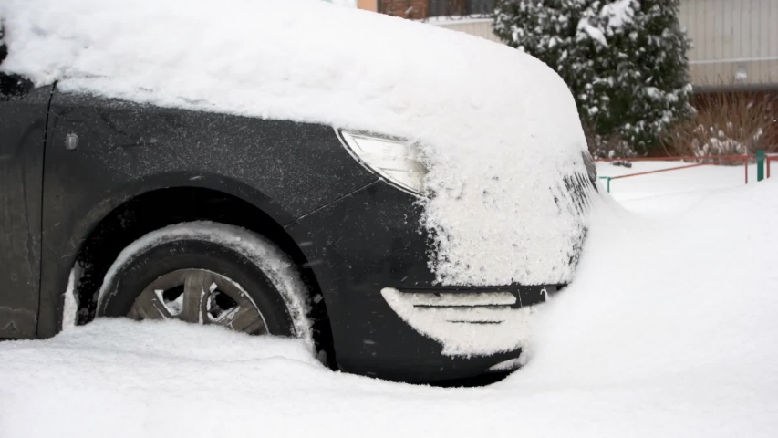 Black car covered in deep winter snow car after heavy snow storm