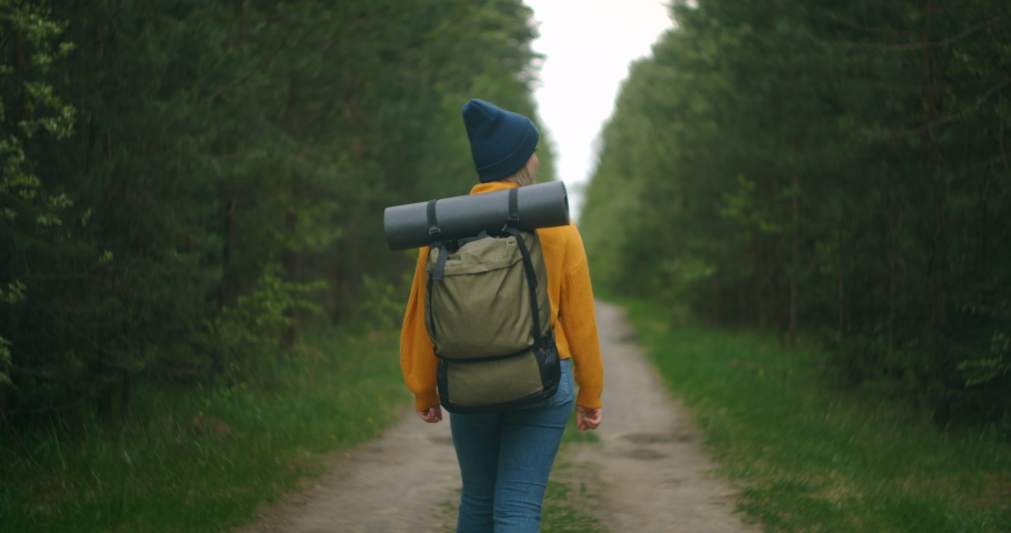 Back view from the bottom and side: a Woman traveling on foot in a yellow sweater and hat on a forest road with a backpack and looking at trees and nature. Alone on a trip. The concept of freedom  | Shutterstock HD Video #1056929558