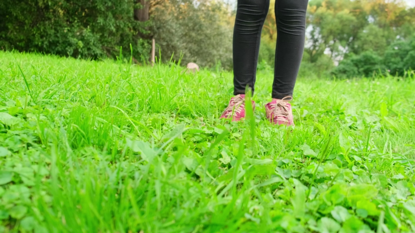 The girl in red sneakers is on the green grass in the direction of the camera. | Shutterstock HD Video #1056930902