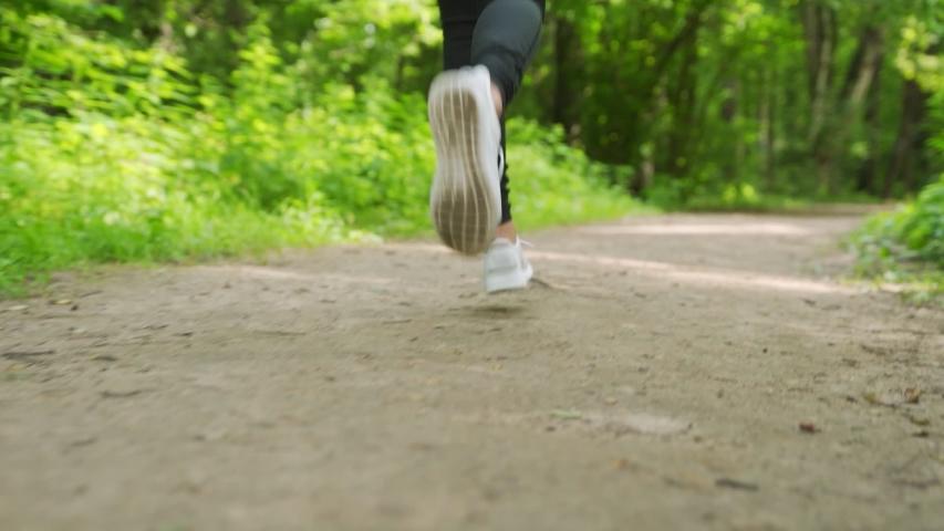 Back view of a girl's feet running through a green forest | Shutterstock HD Video #1056931589