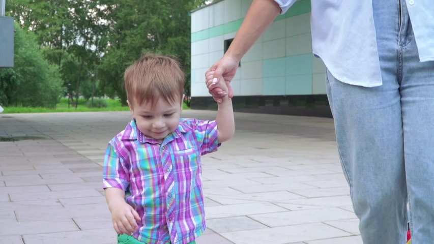 The boy holds his mother's hand and goes down the steps | Shutterstock HD Video #1056931820